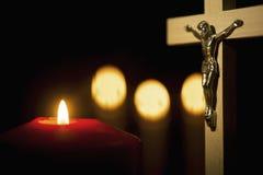 Hölzernes Kreuz mit brennenden Kerzen im Hintergrund stockfotografie
