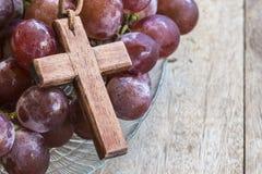Hölzernes Kreuz und Traube auf hölzernem Hintergrund Lizenzfreies Stockfoto