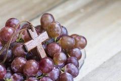 Hölzernes Kreuz und Traube auf hölzernem Hintergrund Lizenzfreie Stockfotos
