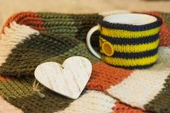 Hölzernes leeres Herz auf dem Hintergrund von Schalen in einer gestrickten Abdeckung Stockfotos
