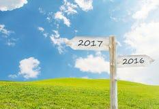 Hölzernes leeres Zeichen mit Text 2017 über grüner Rasenfläche mit Clo Lizenzfreie Stockbilder