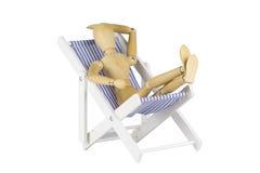 Hölzernes Mannequin auf einem Strandstuhl stockbild