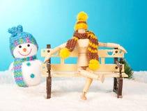 Hölzernes Mannequin auf einer schneebedeckten Bank Lizenzfreie Stockfotos