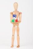Hölzernes Mannequin, das bunte Blockwürfel hält Stockbild