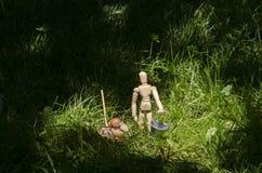 Hölzernes Mannequin im grünen Gras mit Miniatureimer und Schaufel Stockfoto