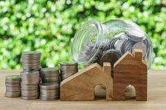 hölzernes Miniatur- Haus mit Stapel Münzen und Münzen im Glas-ja Stockfotografie