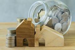 hölzernes Miniatur- Haus mit Stapel Münzen und Münzen im Glas-ja Stockfoto