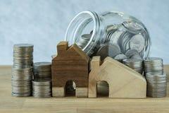 hölzernes Miniatur- Haus mit Stapel Münzen und Münzen im Glas-ja Lizenzfreies Stockbild