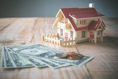 hölzernes Musterhaus mit Geld auf hölzerner Tabelle mit dem Kopienraum gelesen Lizenzfreies Stockbild