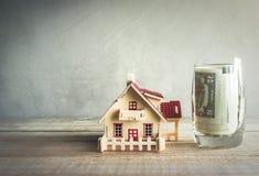 hölzernes Musterhaus mit Geld im Glas auf hölzerner Tabelle mit Co stockfotos