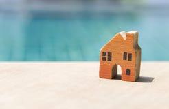 Hölzernes orange Miniaturhaus über unscharfem Swimmingpoolhintergrund Stockfoto