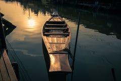 Hölzernes Paddelboot der Weinleseart und Reflexionsschatten der Morgensonne auf Amphawa-Kanal, sich hin- und herbewegender Markt  stockfotografie