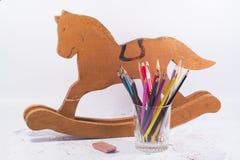 Hölzernes Pferd, Bleistifte und Radiergummi Stockfotografie