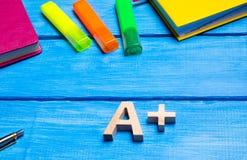 Hölzernes Plus des Buchstaben A auf dem Student ` s Schreibtisch Schulbedarf auf einem blauen Holztisch Das Konzept von Highschoo stockfotos
