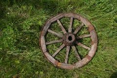 Hölzernes Rad auf einem Hintergrund des grünen Grases Lizenzfreie Stockfotos