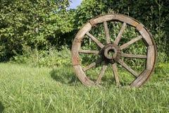 Hölzernes Rad auf einem Hintergrund des grünen Grases Lizenzfreies Stockfoto