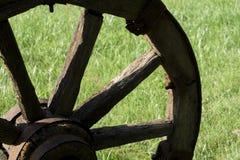 Hölzernes Rad auf einem Hintergrund des grünen Grases Stockbilder