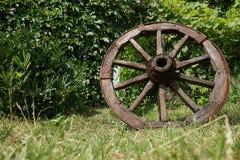Hölzernes Rad auf einem Hintergrund des grünen Grases Stockbild