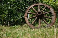 Hölzernes Rad auf einem Hintergrund des grünen Grases Lizenzfreie Stockfotografie