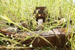 Hölzernes Rad auf einem Hintergrund des grünen Grases Stockfoto
