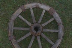 Hölzernes Rad auf einem Hintergrund des grünen Grases Lizenzfreies Stockbild