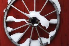 Hölzernes Rad auf roter Wand mit Schnee Lizenzfreies Stockfoto