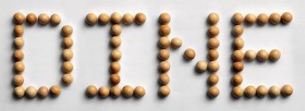 Hölzernes Reißnagel-Wort-Kunst ` speisen ` Stockfotografie