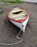 Hölzernes Reihenboot der alten Weinlese auf dem Strand entlang der Küstenlinie Stockfotos