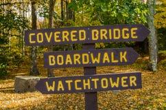 Hölzernes Richtungszeichen an einer Gabel entlang Forest Path Lizenzfreie Stockbilder