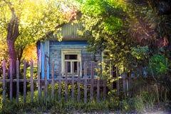 Hölzernes rustikales altes Haus unter dem Grün stockbild
