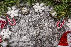 Hölzernes rustikales Weihnachtsschneebedeckter Hintergrund mit Süßigkeit, Hut, Dekorationen und grüne Kiefernniederlassungen und  Lizenzfreies Stockbild
