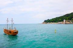 Hölzernes Schiff auf dem Hintergrund von Meer und von Vegetation Stockfotos