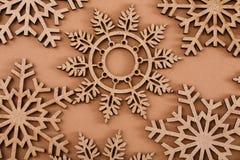 Hölzernes Schneeflockenmuster auf beige Hintergrund Stockbilder