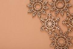 Hölzernes Schneeflockenmuster auf beige Hintergrund Stockbild