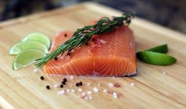 Hölzernes Schneidebrett im Küchentisch mit frischen roten Lachsen fischen Salzpfeffer und kalken kochfertiges lizenzfreie stockfotografie