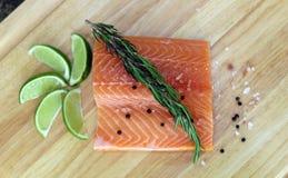 Hölzernes Schneidebrett im Küchentisch mit frischen roten Lachsen fischen Salzpfeffer und kalken kochfertiges stockbilder