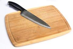 Hölzernes Schneidebrett mit dem großen Messer, das auf Weiß legt Lizenzfreie Stockfotos