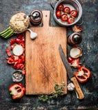 Hölzernes Schneidebrett mit organischem Gemüse und Küchenmesser, gesunder Lebensmittelhintergrund, Draufsicht Stockfotos