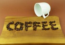 Hölzernes Schneidebrett mit Wort des Kaffees mit Kaffeebohnen Stockfotos
