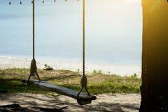 Hölzernes Schwingen auf dem Strand mit Sonnenuntergang lizenzfreie stockfotos