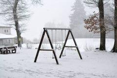 Hölzernes Schwingen auf einem Waldspielplatz bedeckt im Schnee im Winter stockbild