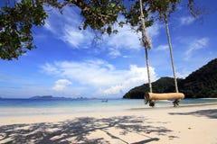 Hölzernes Schwingen auf Strand unter bluesky Stockfotografie