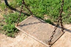Hölzernes Schwingen, das von den Ketten im Yard hängt Lizenzfreie Stockfotografie