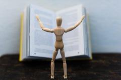 Hölzernes Spielzeug im Bild eines Mannes auf dem Hintergrund eines Buches Stockfotos
