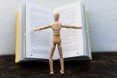 Hölzernes Spielzeug im Bild eines Mannes auf dem Hintergrund eines Buches Stockfotografie