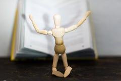 Hölzernes Spielzeug im Bild eines Mannes auf dem Hintergrund eines Buches Lizenzfreie Stockbilder