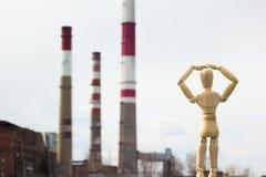 Hölzernes Spielzeug im Bild eines Mannes vor dem hintergrund der Pfeifen einer Fabrik Stockbild