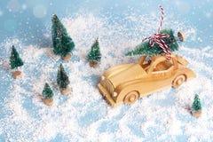 Hölzernes Spielzeugauto mit Weihnachtsbaum auf dem Dach auf blauer Schneerückseite Stockfotos