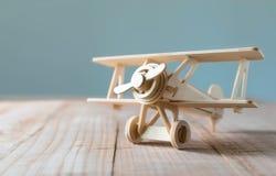Hölzernes Spielzeugflugzeug auf hölzerner Tabelle mit blauem sauberem Hintergrund Lizenzfreies Stockfoto