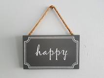 Hölzernes Tag gemalte Aufschrift: glücklich Stockfotos